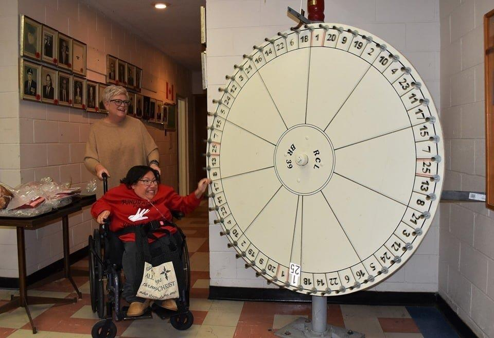 photo of two women spinning a roulette wheel